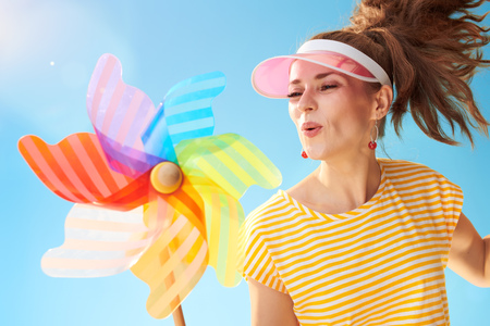 happy fit woman in yellow shirt against blue sky blowing on colorful windmill