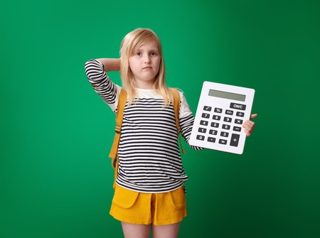 doubting school girl with backpack with calculator isolated on green