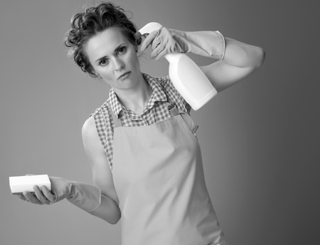 Big cleaning time. tired modern woman in a apron with kitchen sponge wanting to shoot herself from a bottle of detergent against background