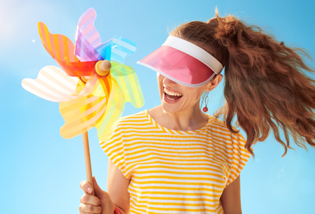 cheerful healthy woman in yellow shirt against blue sky hiding behind sun visor holding colorful windmill