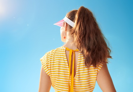 Seen from behind fit woman in yellow shirt standing against blue sky