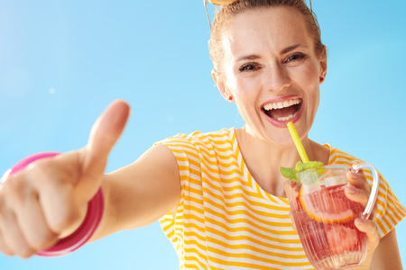 smiling healthy woman in yellow shirt against blue sky with refreshing cocktail showing thumbs up Фото со стока