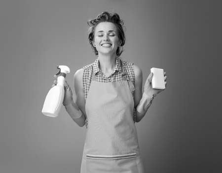 Big cleaning time. smiling modern woman in a apron with kitchen sponge and a bottle of detergent isolated on