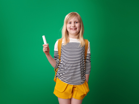 smiling pupil with backpack holding a peace of chalk isolated on green background