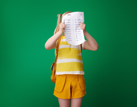 angry school girl with backpack hiding behind a bad grade test isolated on green background