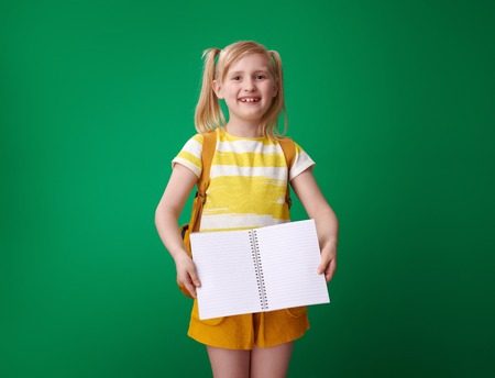 smiling school girl with backpack showing an open notebook isolated on green background