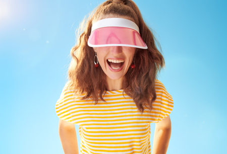 cheerful young woman in yellow shirt against blue sky hiding behind sun visor