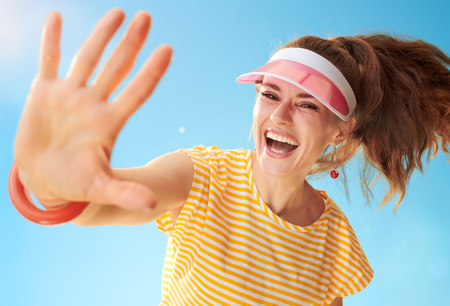 happy healthy woman in yellow shirt against blue sky high five Stok Fotoğraf