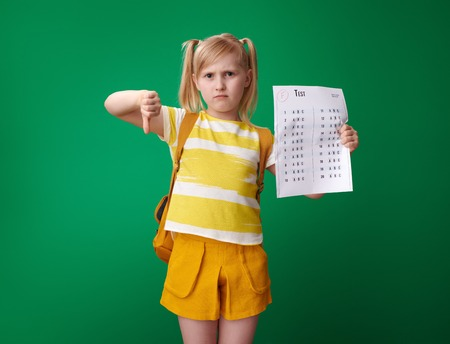 sad school girl with backpack with a bad grade test showing thumbs down isolated on green Stock Photo