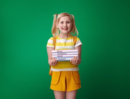 happy pupil with backpack with schoolbooks isolated on green