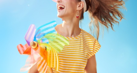happy fit woman in yellow shirt against blue sky with colorful windmill looking into the distance