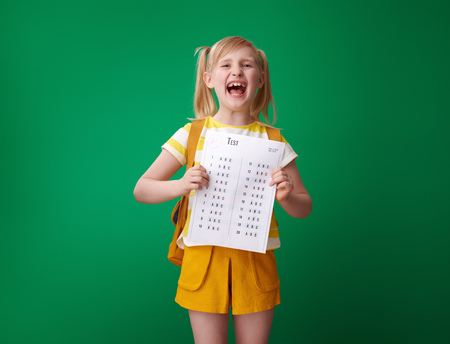 happy pupil with backpack holding an excellent grade test isolated on green Banco de Imagens