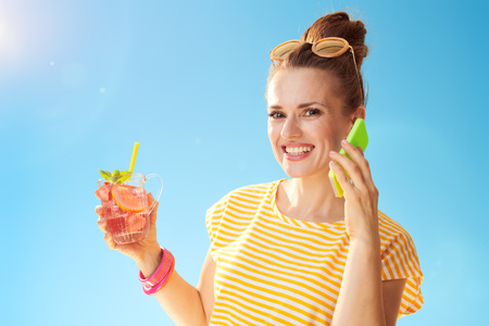 happy healthy woman in yellow shirt against blue sky with refreshing cocktail using a cell phone