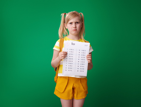 unhappy pupil with backpack holding a bad grade test isolated on green background Banco de Imagens