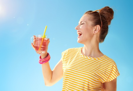 smiling fit woman in yellow shirt against blue sky with refreshing cocktail