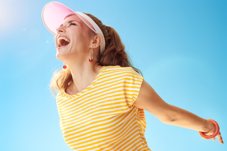 smiling active woman in yellow shirt against blue sky rejoicing