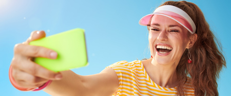 happy young woman in yellow shirt against blue sky taking selfie with smartphone