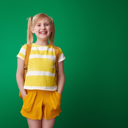 happy pupil with backpack isolated on green Stockfoto