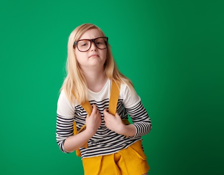 tired school girl with backpack on green background