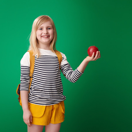 smiling school girl with backpack holding an apple against green background Stock Photo