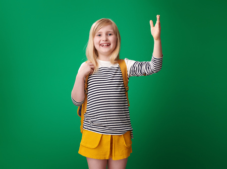 happy pupil with backpack with raised hand to answer on green background Stockfoto