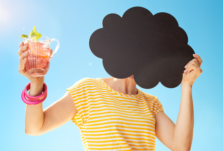 healthy woman in yellow shirt against blue sky with refreshing cocktail hiding behind cloud shaped blackboard