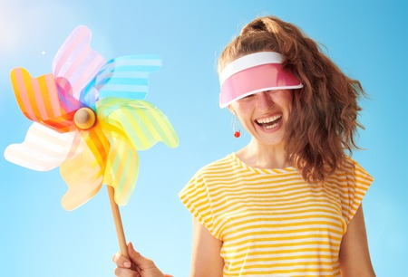 cheerful young woman in yellow shirt against blue sky hiding behind sun visor holding colorful windmill