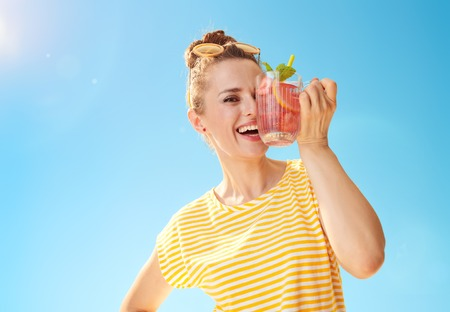 happy young woman in yellow shirt against blue sky with refreshing cocktail having fun time