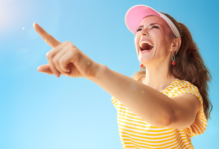 happy active woman in yellow shirt against blue sky pointing at something