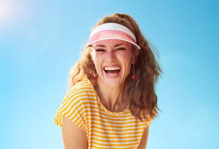 Portrait of happy young woman in yellow shirt against blue sky