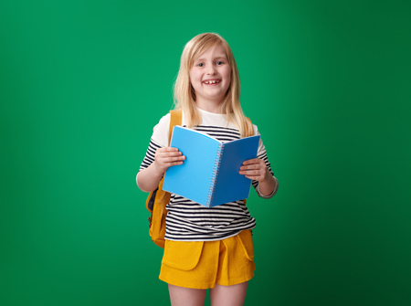 happy school girl with backpack with open notebook on green background