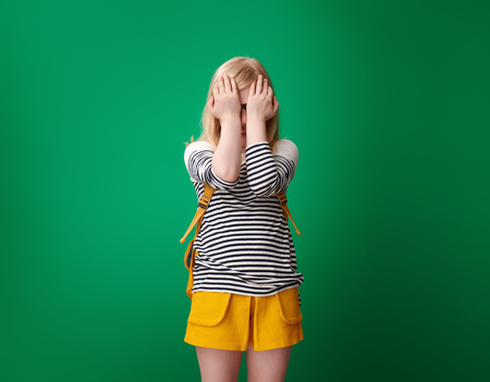 Portrait of stressed pupil with backpack isolated on green Stockfoto