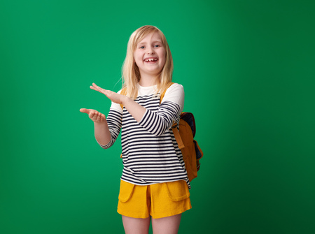 smiling school girl with backpack clapping isolated on green background