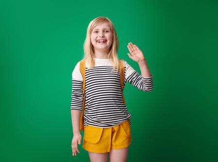 happy school girl with backpack handwaving on green background