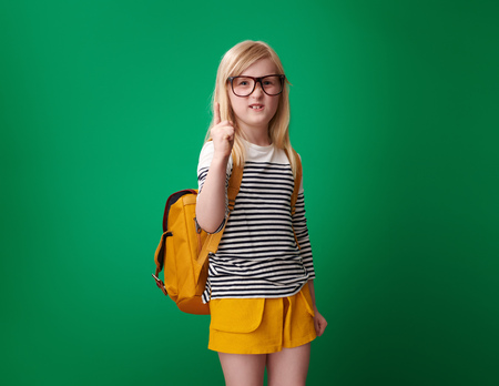 annoyed pupil with backpack threatening with finger against green background