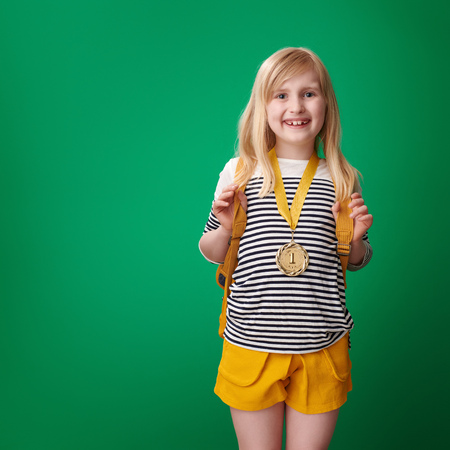 smiling school girl with backpack with gold medal on green background