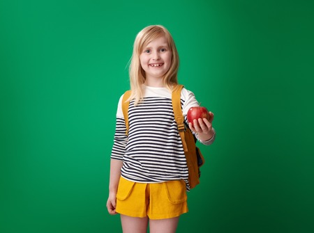 happy pupil with backpack giving an apple isolated on green