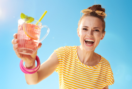 smiling healthy woman in yellow shirt against blue sky giving refreshing cocktail