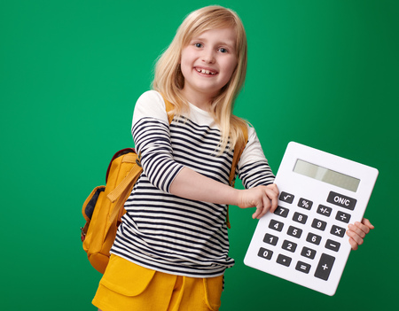 happy school girl with backpack showing calculator isolated on green background 스톡 콘텐츠