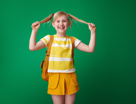 Portrait of happy pupil with backpack with tails against green background Stockfoto