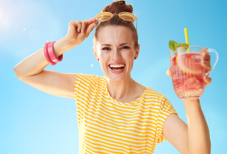 smiling healthy woman in yellow shirt against blue sky showing refreshing cocktail