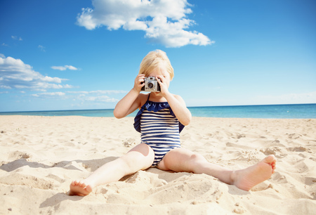 Girl in swimwear taking photo with retro film photo camera on the beach
