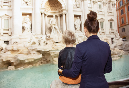 Seen from behind young mother and daughter tourists at Trevi Fountain exploring attractions Stock Photo