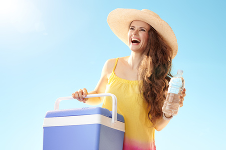 Happy active woman in straw hat with blue plastic cooler box and bottle of cold water looking at copy space against blue sky