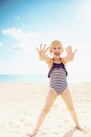Smiling girl in swimsuit on the beach showing empty palms