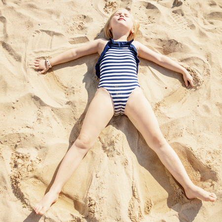 Relaxed child in beachwear laying on sand and making angel on the beach Archivio Fotografico