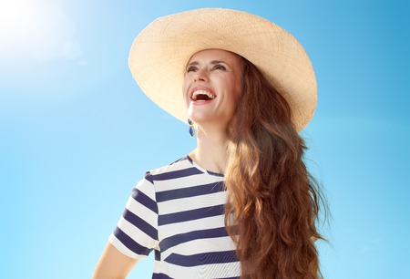 Happy modern woman in straw hat looking into the distance against blue sky