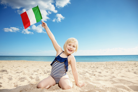 Happy child in swimsuit on the seacoast showing Italian flag