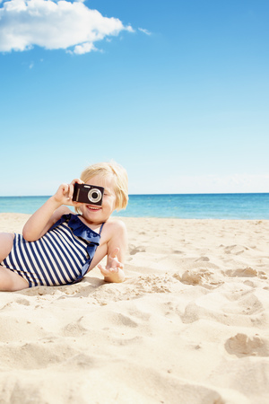Smiling girl in swimsuit taking photo with digital camera on the beach