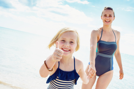 Smiling modern mother and child in swimwear on the seashore showing thumbs up while coming out of sea
